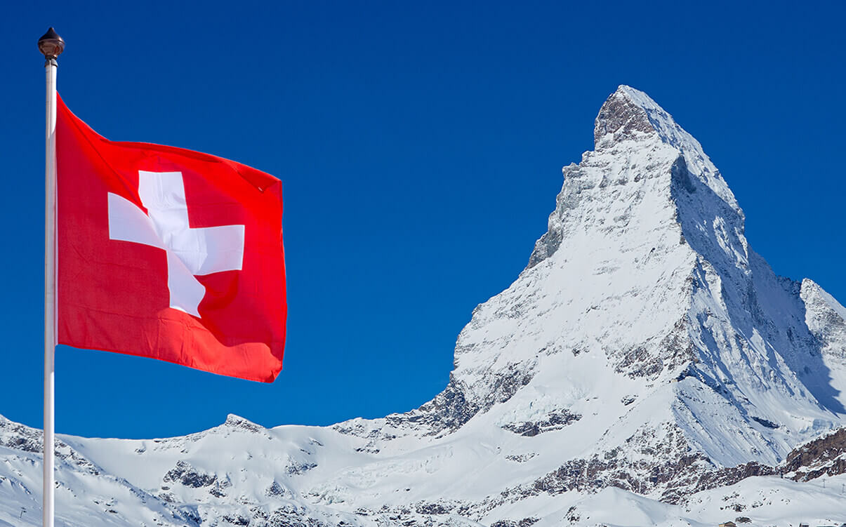 Image of a Swiss flag in front of the Matterhorn